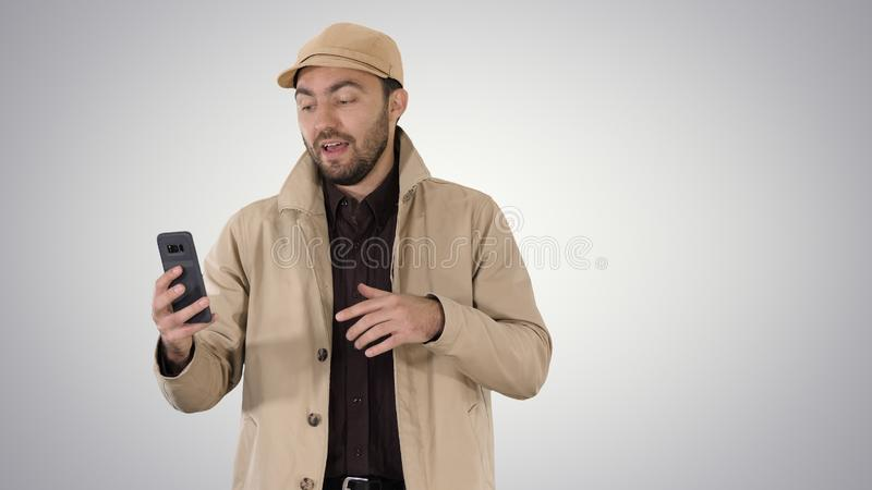 M?ody cz?owiek robi wideo wezwaniu od jego telefonu kom?rkowego na gradientowym tle podczas gdy chodz?cy fotografia stock