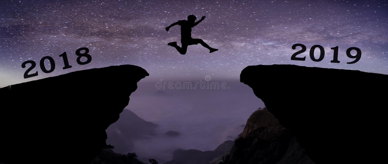 M?ody cz?owiek skacze mi?dzy 2018, 2019 rok i z gwiazdami na przerwie wzg?rze sylwetki wiecz?r kolorowy i nad nocnym niebem obrazy royalty free