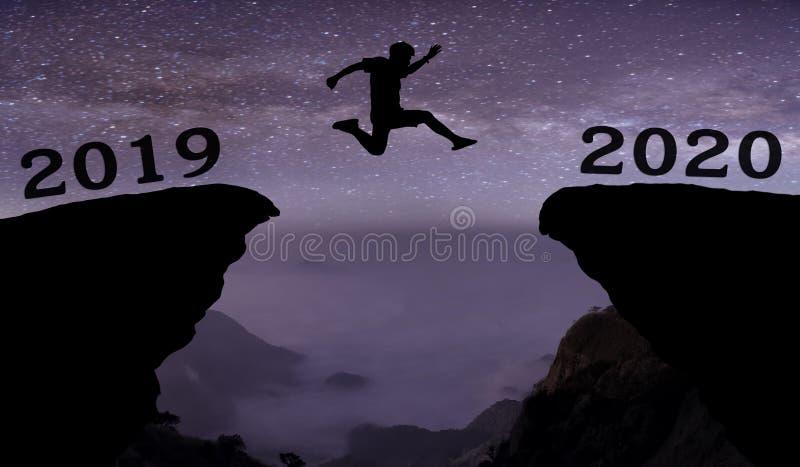 M?ody cz?owiek skacze mi?dzy 2019, 2020 rok i z gwiazdami na przerwie wzg?rze sylwetki wiecz?r kolorowy i nad nocnym niebem ilustracji