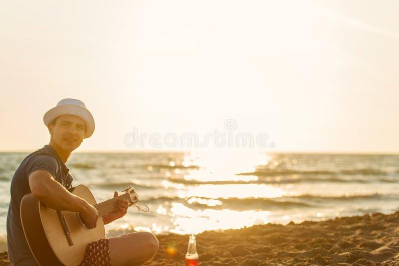 M?ody cz?owiek sztuki gitara na pla?y i cieszy si? w zmierzchu zdjęcie royalty free