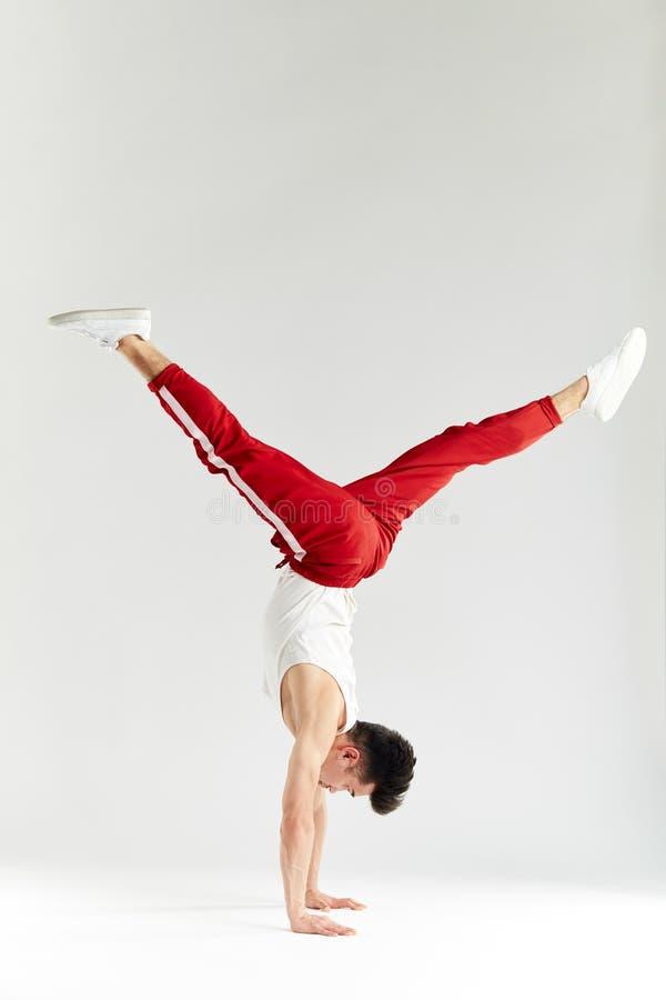 M?ody cz?owiek w czerwonych sweatpants robi handstand na r?kach na bia?ym tle zdjęcia stock