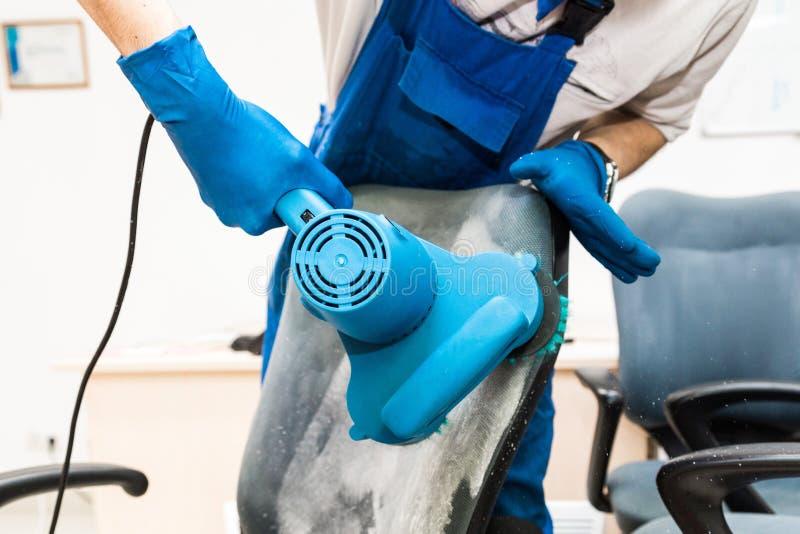M?ody cz?owiek w workwear i gumy r?kawiczkach czy?ci biurowego krzes?a z fachowym wyposa?eniem fotografia stock