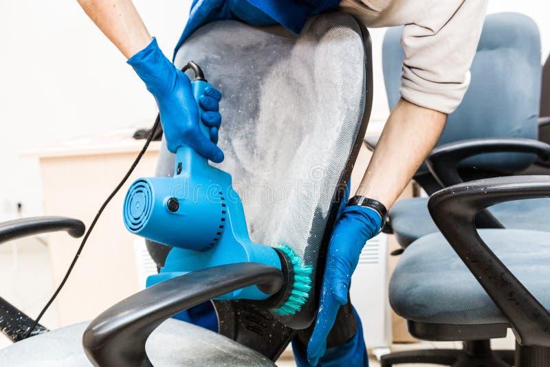 M?ody cz?owiek w workwear i gumy r?kawiczkach czy?ci biurowego krzes?a z fachowym wyposa?eniem zdjęcia stock