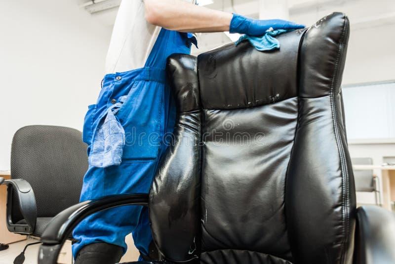 M?ody cz?owiek w workwear i gumy r?kawiczkach czy?ci biurowego krzes?a z fachowym wyposa?eniem fotografia royalty free