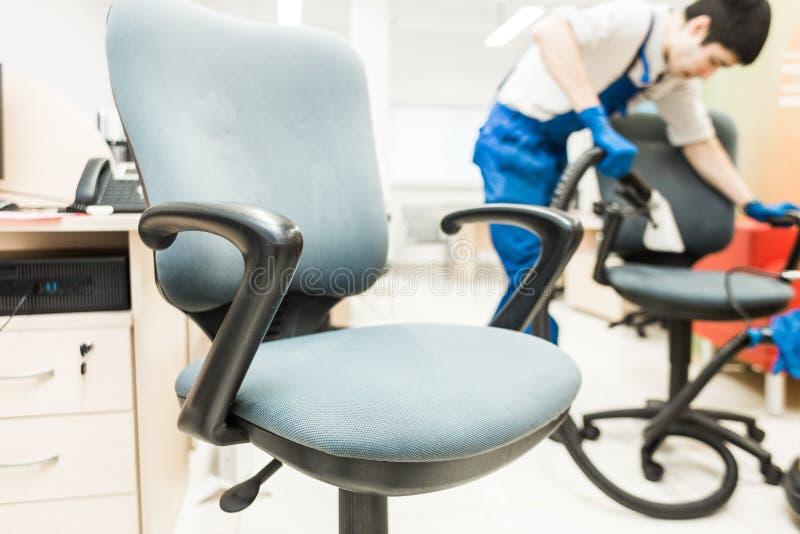 M?ody cz?owiek w workwear i gumy r?kawiczkach czy?ci biurowego krzes?a z fachowym wyposa?eniem obrazy stock