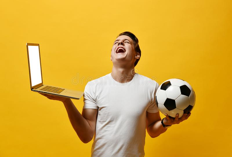M?ody cz?owiek z laptopem i pi?ki no?nej pi?k? obraz royalty free