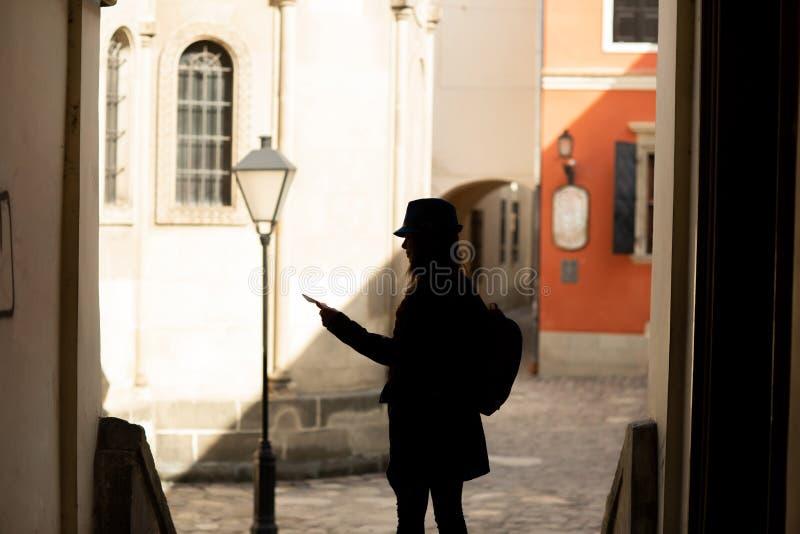 M?ody elegancki kobiety odprowadzenie na starej grodzkiej ulicie, podr??y z plecakiem i b??kitnym kapeluszu, 1990 buduj?cych Lviv fotografia royalty free