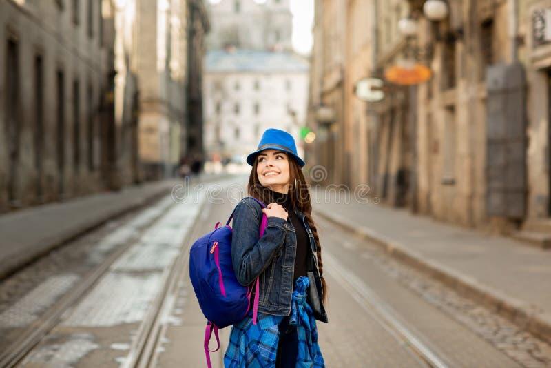M?ody elegancki kobiety odprowadzenie na starej grodzkiej ulicie, podr??y z plecakiem i b??kitnym kapeluszu, 1990 buduj?cych Lviv zdjęcia royalty free