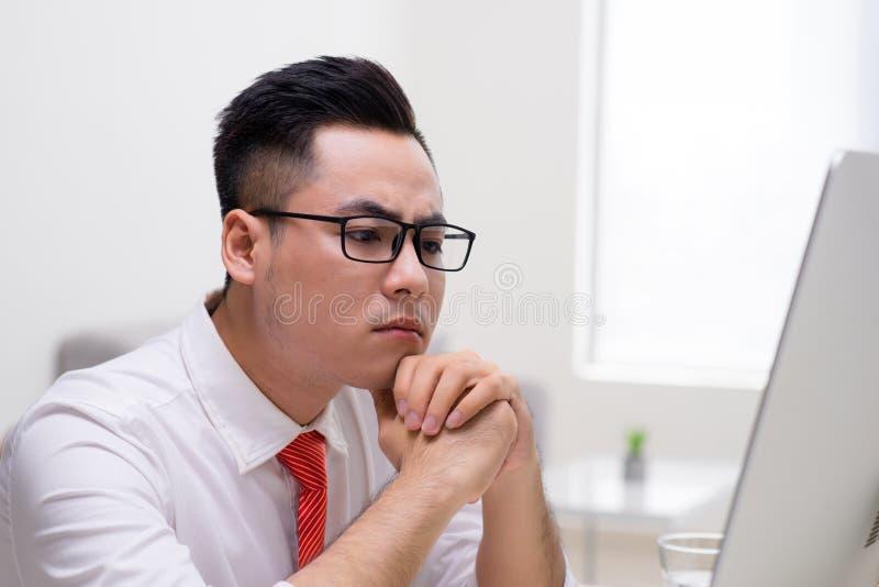 M?ody elegancki pracownik przy biurowym dzia?aniem z komputerem i g??wkowaniem dlaczego rozwi?zywa? trudne zadanie fotografia stock