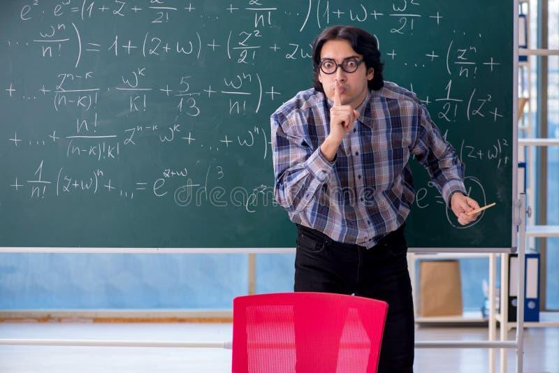 M?ody ?mieszny nauczyciel matematyki przed chalkboard obraz stock