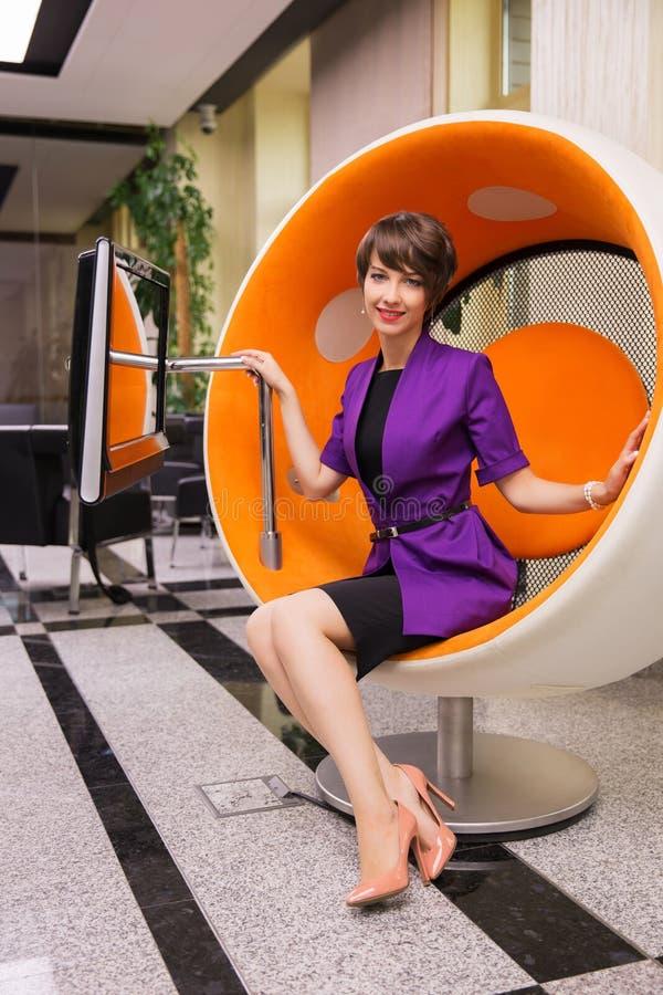 M?ody mody biznesowej kobiety obsiadanie na komputerowym krze?le w biurze zdjęcia stock