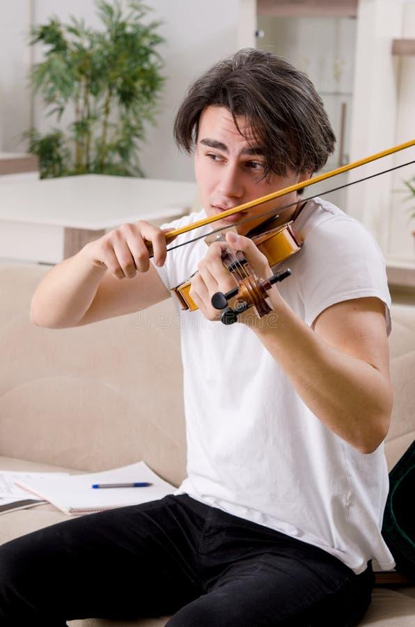 M?ody muzyka m??czyzna ?wiczy bawi? si? skrzypce w domu fotografia royalty free