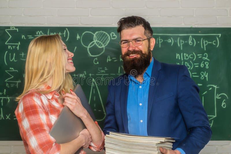 M?ody nauczyciel blisko chalkboard w szkolnej sala lekcyjnej Ucznia kampusu edukaci wiedzy poj?cie Dru?ynowy wsp??praca fotografia stock