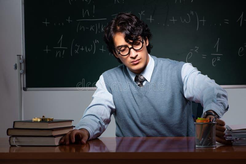 M?ody nauczyciel matematyki przed chalkboard obrazy royalty free