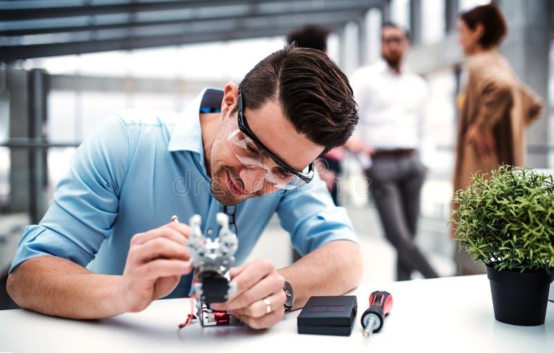 M?ody naukowiec z mechaniczn? r?ki pozycj? w biurze lub biznesmen, pracuje obrazy royalty free