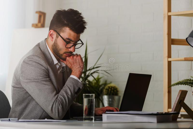 M?ody nowo?ytny biznesmena enterpreneur obsiadanie w jego biurowym dzia?aniu na komputerze obrazy stock