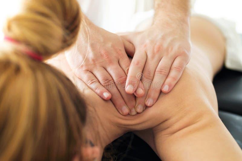 M?ody physiotherapist robi tylnemu traktowaniu pacjent w fizjoterapia pokoju zdjęcie royalty free
