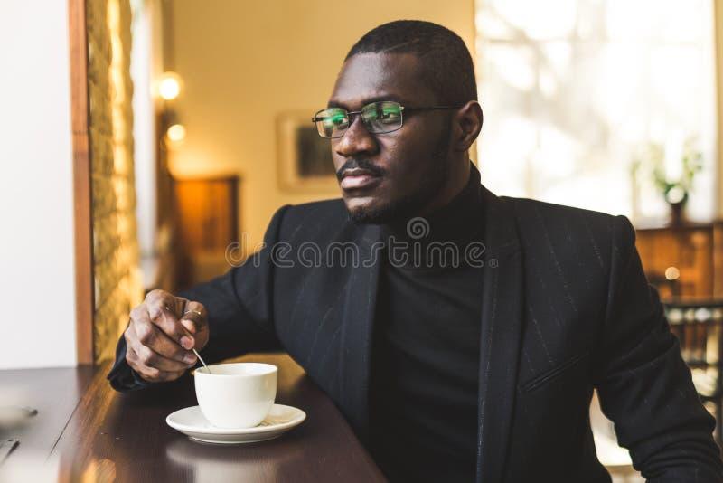 M?ody przystojny ciemnosk?ry biznesmen w kawiarni z fili?ank? herbata fotografia stock