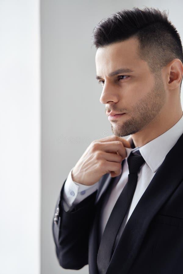 M?ody przystojny m??czyzna w eleganckim kostiumu przystosowywa jego krawat fotografia stock