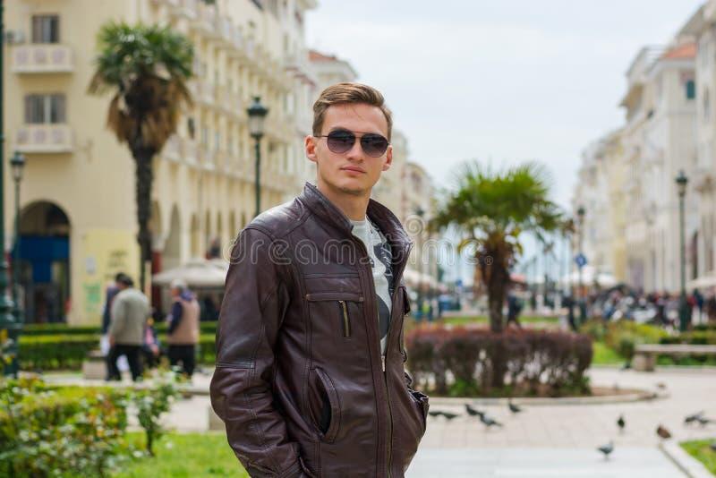 M?ody przystojny m??czyzna w okularach przeciws?onecznych, turysta, na zwyczajnej Aristotle ulicie w centrum Saloniki, Grecja fotografia royalty free