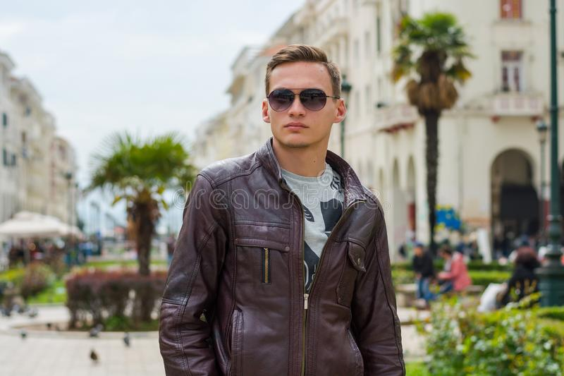 M?ody przystojny m??czyzna w okularach przeciws?onecznych, turysta, na zwyczajnej Aristotle ulicie w centrum Saloniki, Grecja zdjęcia royalty free