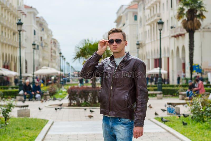 M?ody przystojny m??czyzna w okularach przeciws?onecznych, turysta, na zwyczajnej Aristotle ulicie w centrum Saloniki, Grecja obraz stock