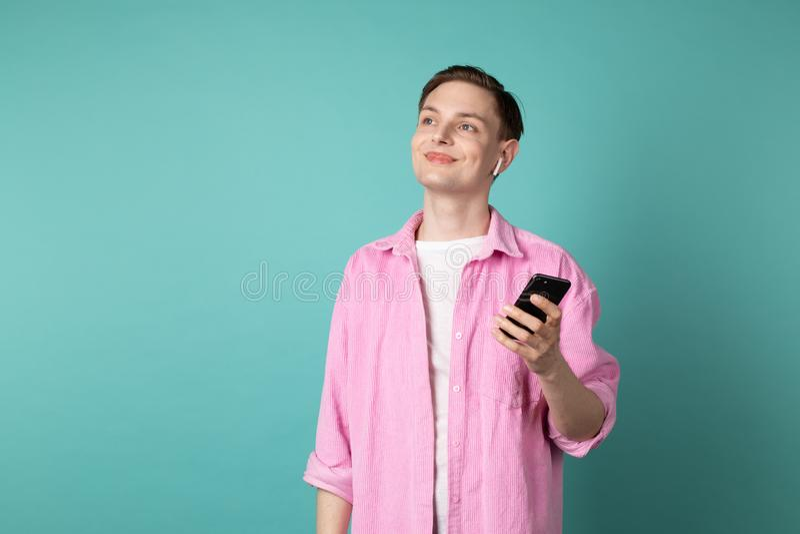 M?ody przystojny m??czyzna w r??owej koszula z telefonem w r?kach i bia?ych s?uchawkach zdjęcie royalty free