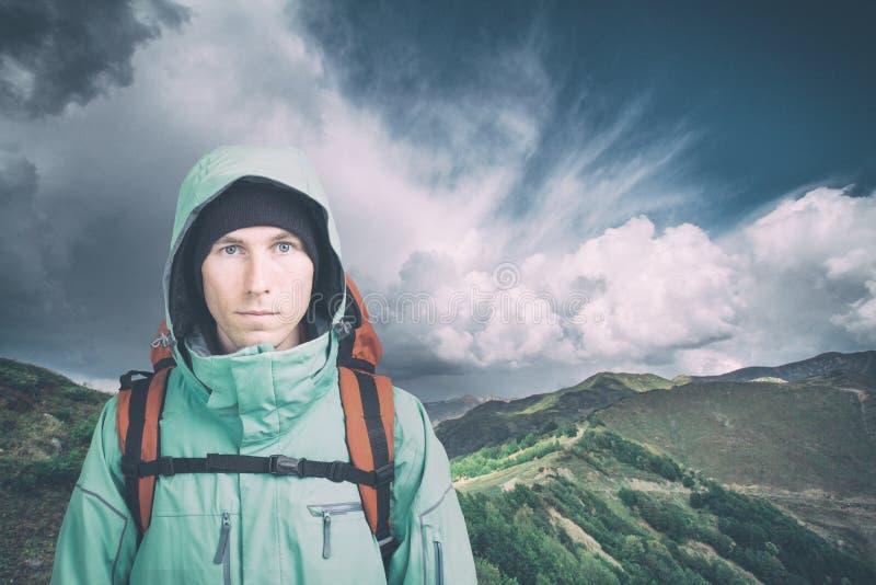 M?ody m?ski wycieczkowicz patrzeje kamer? na chmurnym krajobrazowym tle Frontowy widok aktywny styl ?ycia i turystyka fotografia stock