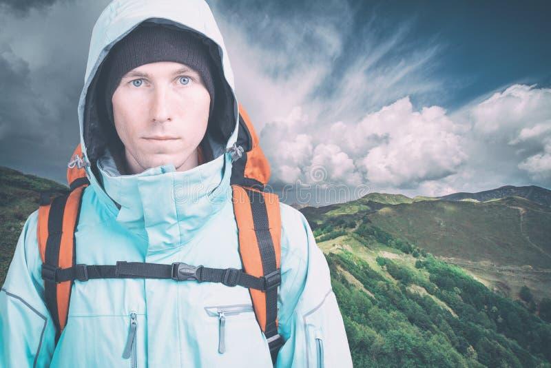M?ody m?ski wycieczkowicz patrzeje kamer? na chmurnym krajobrazowym tle Frontowy widok aktywny styl ?ycia i turystyka obrazy stock