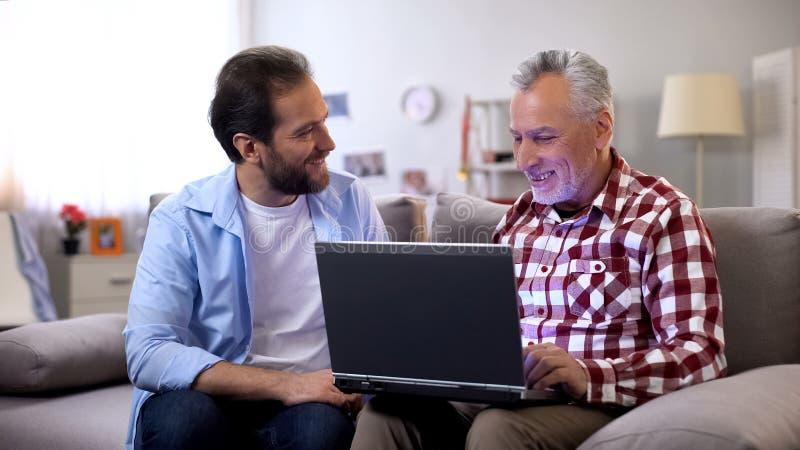 M?ody syn wyja?nia starzej?cego si? ojca dlaczego u?ywa? laptop, nowo?ytne technologie, przyrz?d fotografia stock
