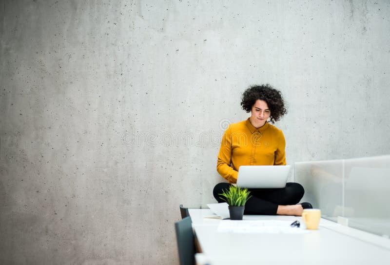 M?ody ucznia, bizneswomanu obsiadanie na biurku w pokoju w lub, u?ywa? laptop obrazy royalty free