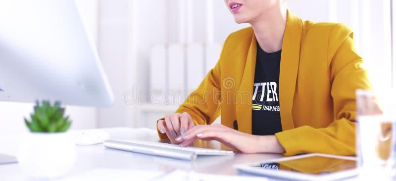 M?ody ufny bizneswoman pracuje przy biurowym biurkiem i pisa? na maszynie z laptopem zdjęcie royalty free