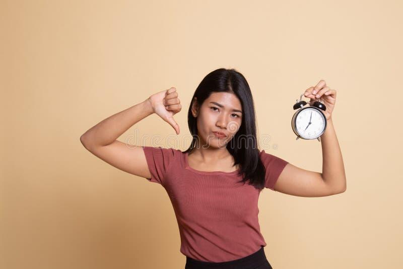 M?odzi Azjatyccy kobieta kciuki zestrzelaj? z zegarem zdjęcia stock
