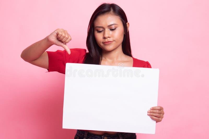 M?odzi Azjatyccy kobiety przedstawienia kciuki zestrzelaj? z bia?ym puste miejsce znakiem obrazy royalty free