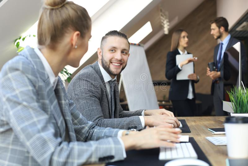 M?odzi ludzie biznesu pracuje na ich komputerach stacjonarnych przy nowo?ytn? powierzchni? biurow? fotografia stock