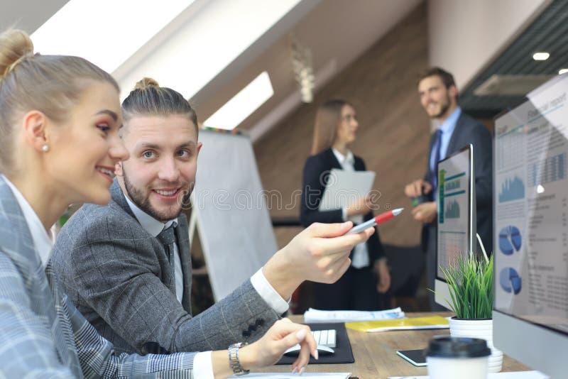 M?odzi ludzie biznesu pracuje na ich komputerach stacjonarnych przy nowo?ytn? powierzchni? biurow? obrazy stock