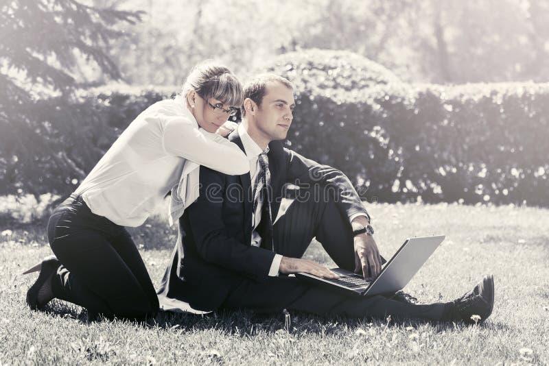 M?odzi ludzie biznesu u?ywa laptop w miasto parku obraz royalty free