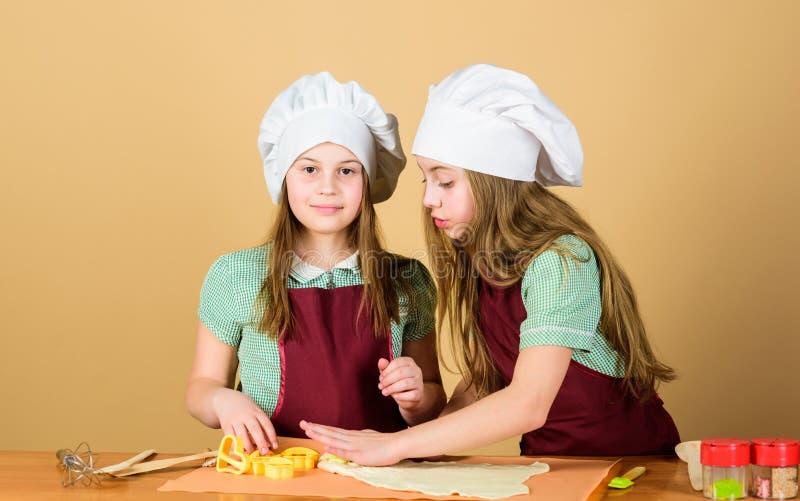 M?odzi piekarzi po wypiekowy przepis Mali piekarzi stacza się pastę na kuchennym stole Małe dziewczynki piec ciastka w piekarzie obrazy stock
