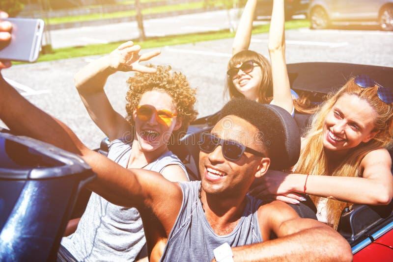 M?odzi przyjaciele bior? selfie w kabrioletu samochodzie fotografia stock