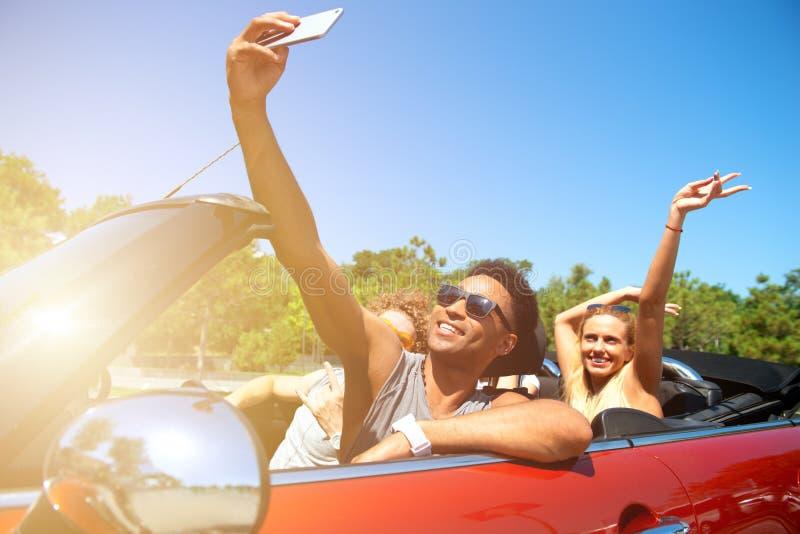 M?odzi przyjaciele bior? selfie w kabrioletu samochodzie zdjęcie stock