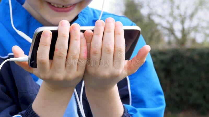 M?os adolescentes do menino com o telefone esperto que escuta ou que fala no parque brit?nico adolescente e conceito social dos m foto de stock royalty free