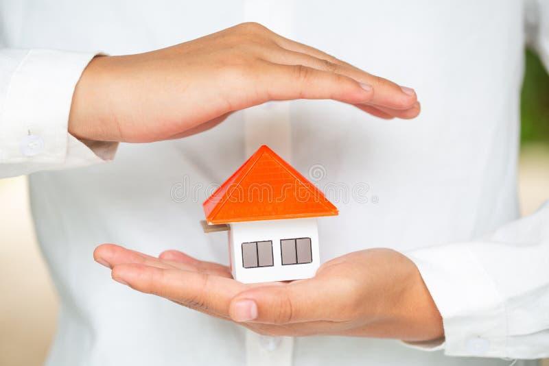 M?os como um telhado de prote??o sobre uma casa, um conceito pequenos do seguro patrimonial e da seguran?a Gesto de prote??o do h imagens de stock