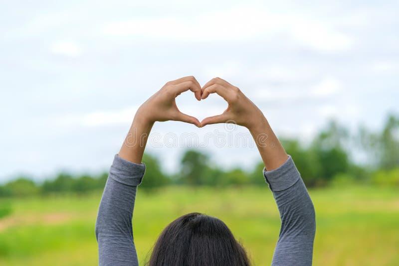 M?os das mulheres sob a forma do gesto de m?o cora??o-dado forma amor, conceito do amor fotografia de stock royalty free