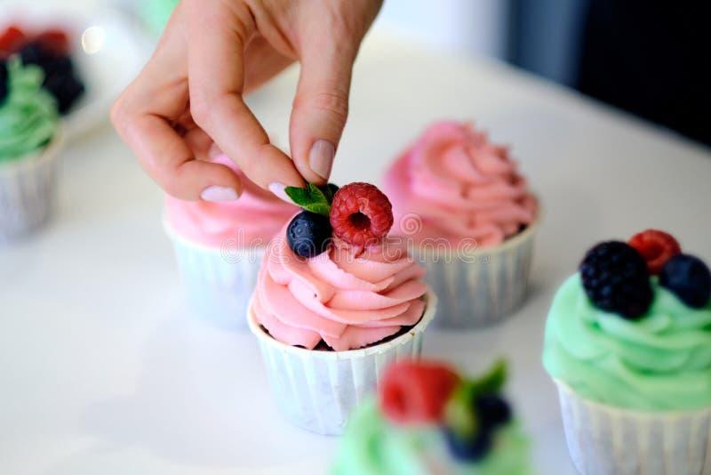 M?os do close up do cozinheiro chefe que decoram queques com bagas coloridas imagem de stock royalty free