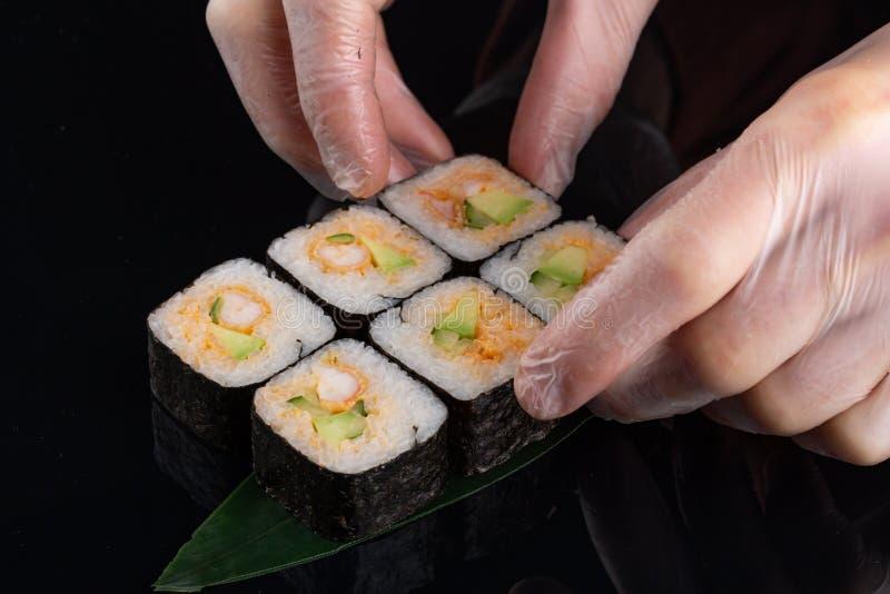 M?os do cozinheiro chefe que preparam o alimento japon?s, cozinheiro chefe que faz o sushi, preparando o rolo de sushi imagem de stock royalty free