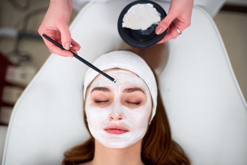 M?os do especialista da cosmetologia que aplicam a m?scara facial usando a escova, fazendo a pele hidratada e saud?vel Mulher atr fotografia de stock royalty free