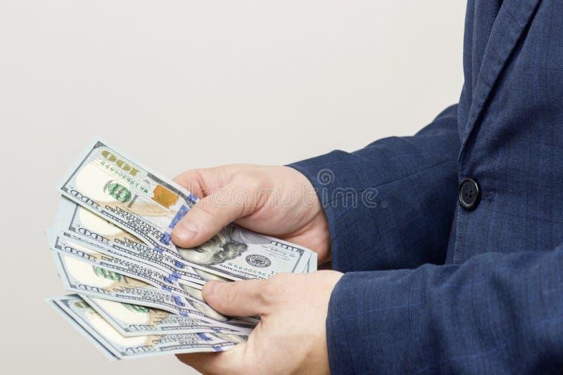 M?os do homem de neg?cios que contam notas de d?lar Conceito das economias, do sal?rio, do pagamento e dos fundos O homem conta c imagens de stock