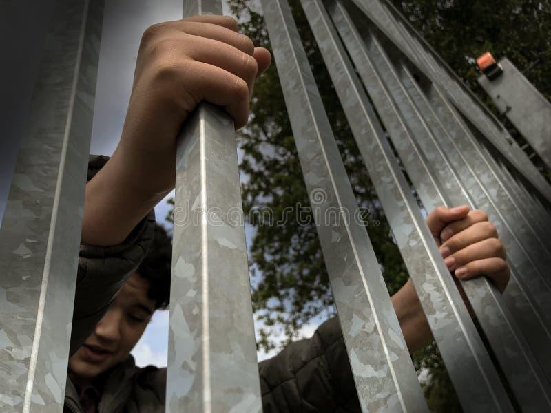 M?os do menino do adolescente que guardam barras de ferro fortes Visto de baixo de Crise do imigrante e do refugiado Cerca da bei imagem de stock royalty free