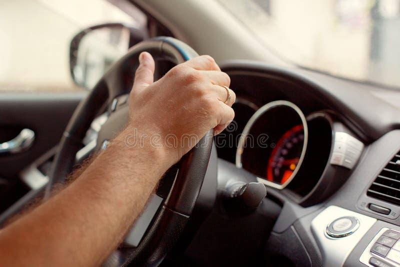 M?os do motorista do homem que guardam o painel da dire??o do carro M?o masculina usando uma engrenagem autom?tica do carro Condu imagens de stock
