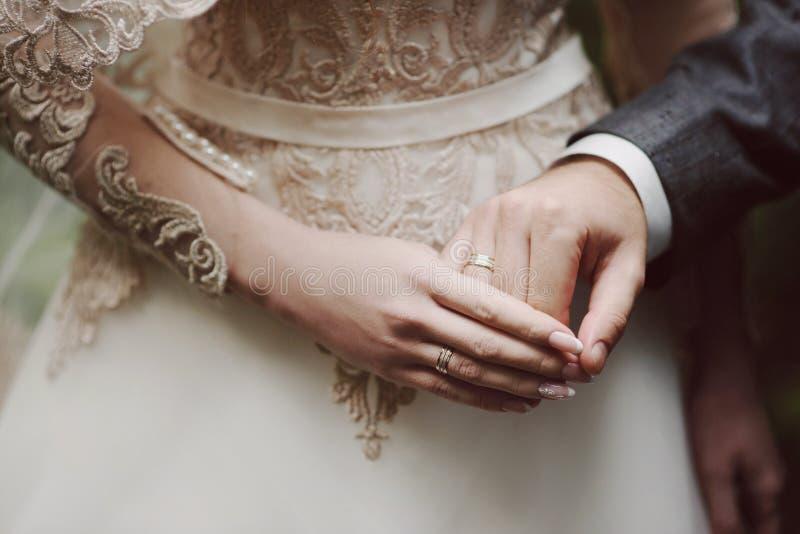 M?os do ` s dos noivos com alian?as de casamento imagens de stock royalty free